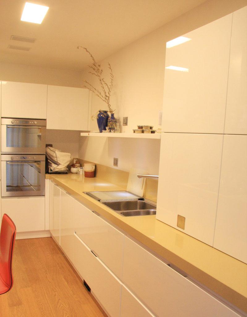 Volumi netti in cucina, organizzata per essere abitabile, con parete attrezzata e tavolo-penisola.  La sequenza del bianco e del rovere chiaro del pavimento si mescola con la quarzite gialla del top.