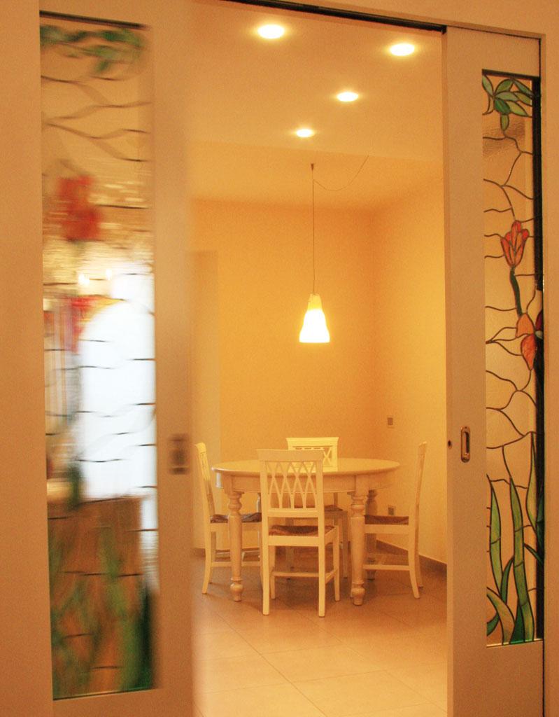 L'obbiettivo era separare la cucina dal living. Ampie porte scorrevoli realizzate su disegno ripropongono lo stile tiffany e ne fanno elemento d'arredo.
