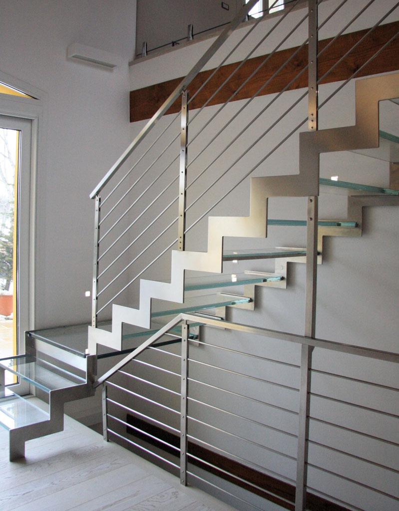La serrata serie  di gradini in vetro, profilati in acciaio ,contro le pareti bianche, costituisce un forte stimolo visivo, che caratterizza l'intero ambiente.